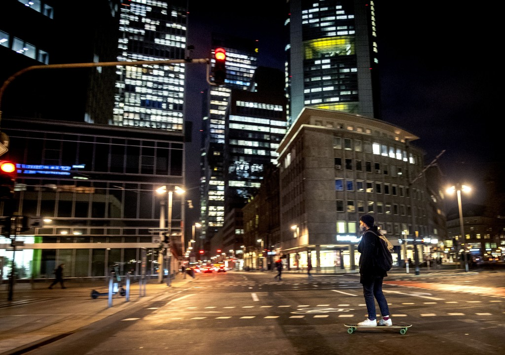 A young man wears a face mask as he crosses a road on his skateboard in downtown Frankfurt, Germany, Thursday, Nov. 26, 2020. The German parliament di...