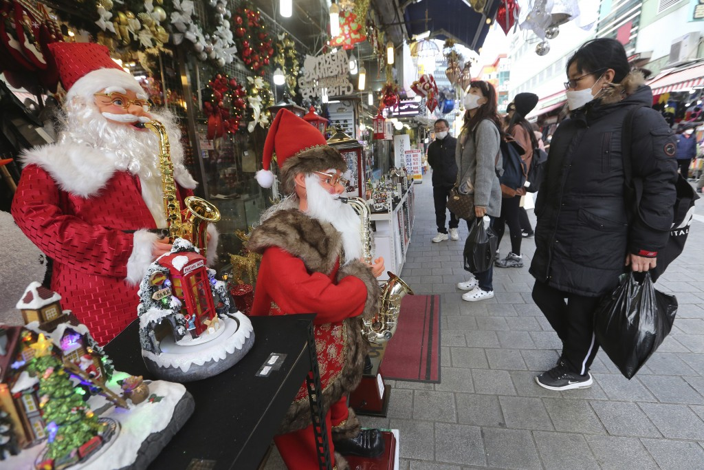 People wearing face masks as a precaution against the coronavirus watch Christmas decorations at a store in Seoul, South Korea, Friday, Nov. 27, 2020....