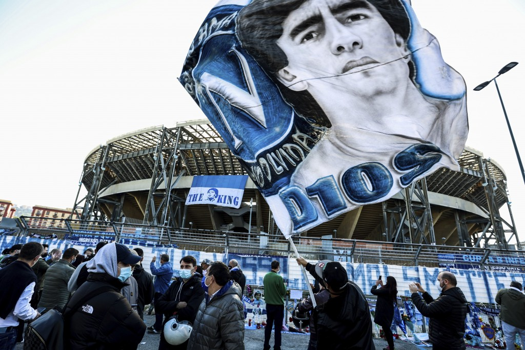 A fan waves a flag with the portrait of soccer legend Diego Armando Maradonain front of the San Paolo stadium in Naples, Italy, Thursday, Nov. 26, 202...