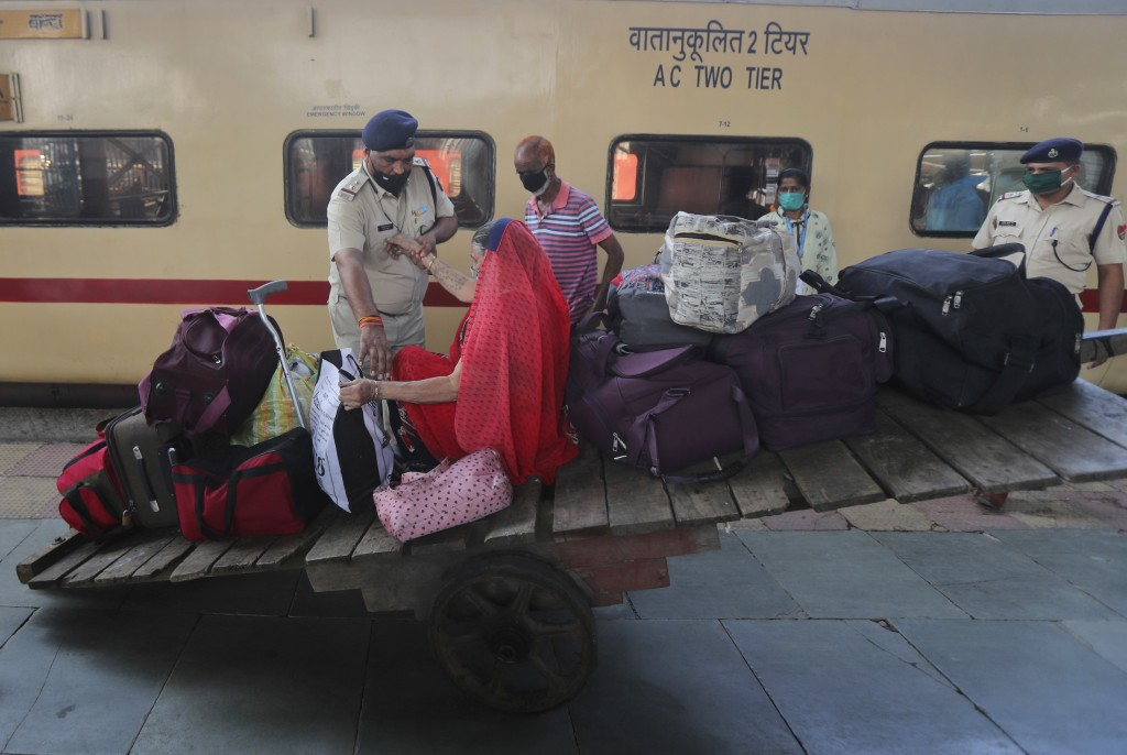 A police officer helps a woman passenger get up to proceed to give her nasal swab sample for COVID-19 testing at a railway station in Mumbai, India, F...