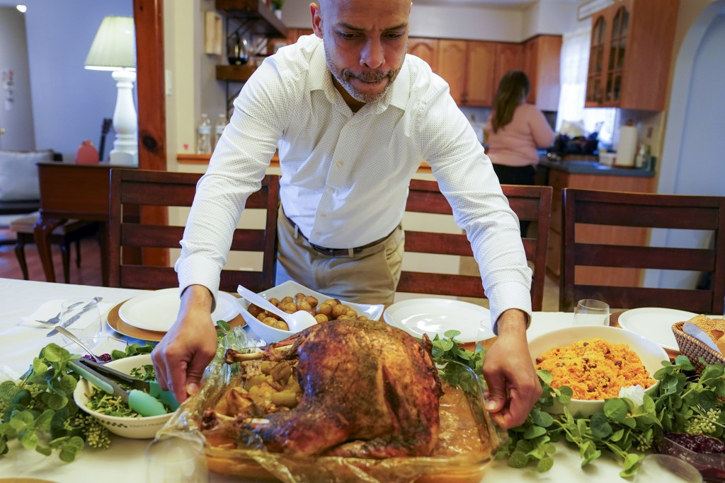 Esdras Zayas places the Thanksgiving turkey on the dining room table before his family celebrates their first holiday without their beloved mother Ana...
