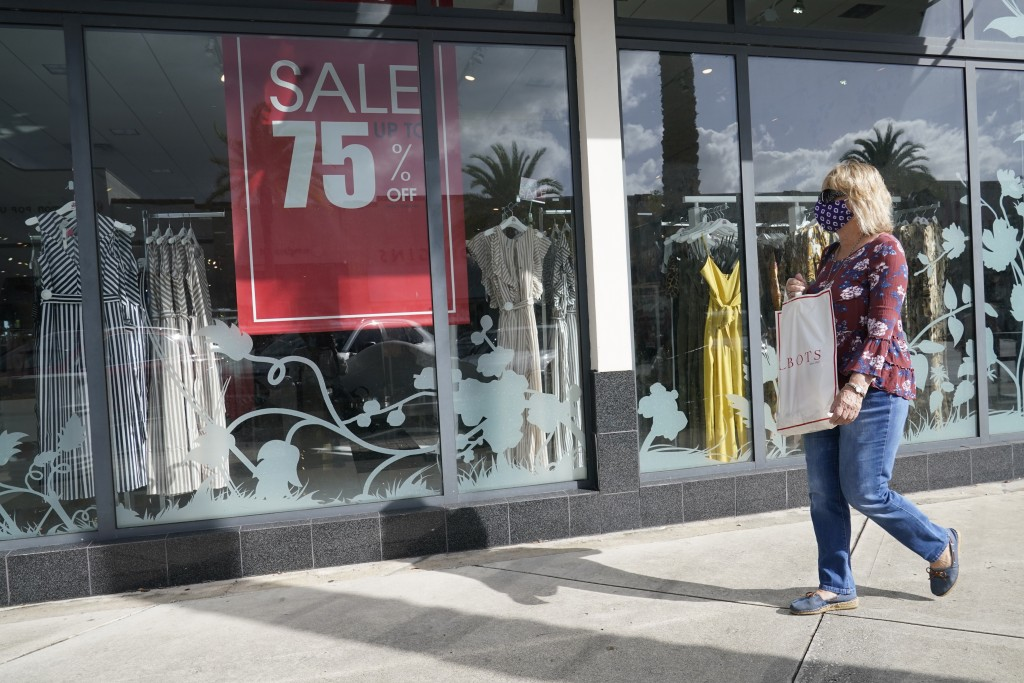A shopper walks by a store, Monday, Nov. 18, 2020 in Pembroke Pines, Fla.  After months of slumping sales and businesses toppling into bankruptcy, Bla...