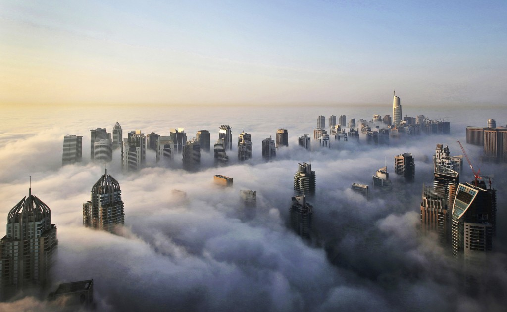 FILE - In this Monday, Oct. 5, 2015 file photo, a thick blanket of early morning fog partially shrouds the skyscrapers of the Marina and Jumeirah Lake...