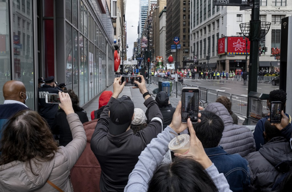 People attempt to take photos as the last floats that are part of the modified Macy's Thanksgiving Day Parade move away in New York, Thursday, Nov. 26...