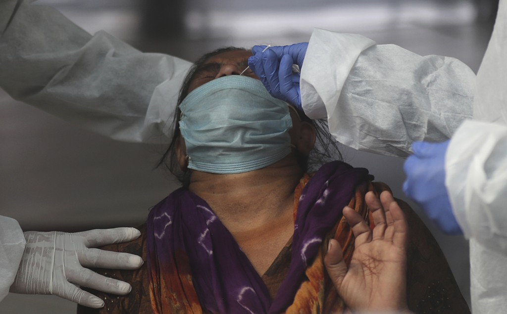 Health workers takes a nasal swab sample of a woman passenger to test for COVID-19 at a train station in Mumbai, India, Friday, Nov. 27, 2020. India h...