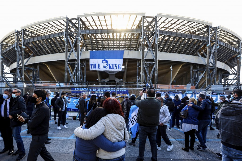 "A couple embraces in front of a banner remembering soccer legend Diego Armando Maradona ""the king"" hanging from the San Paolo stadium in Naples, Italy..."