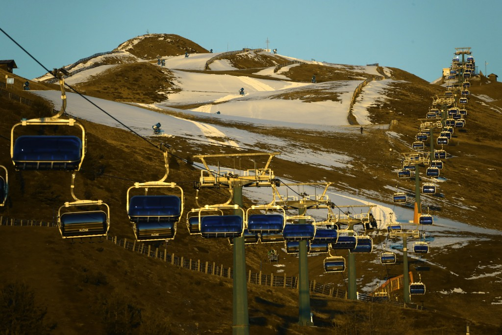 A chairlift is illuminated besides snow makers as the sun sets near Bressanone in northern Italian province of South Tyrol, Italy, Thursday, Nov. 26, ...