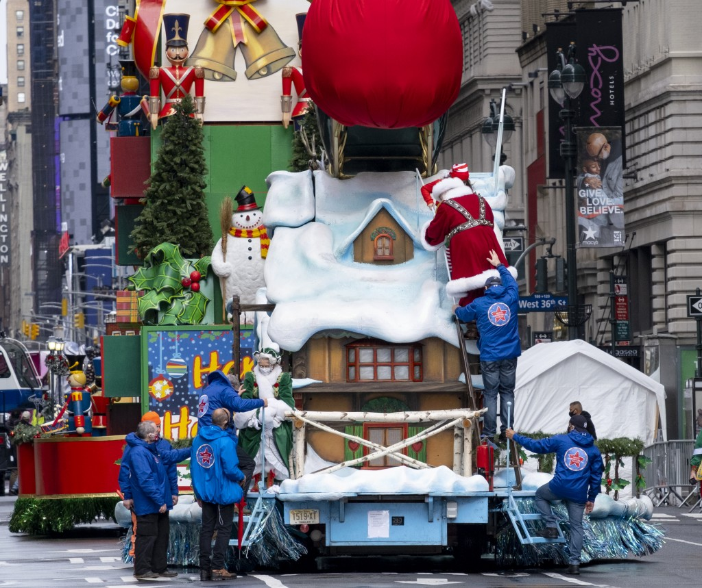 The characters Santa Claus and Mrs. Claus are helped from their float at the end of the modified Macy's Thanksgiving Day Parade in New York, Thursday,...