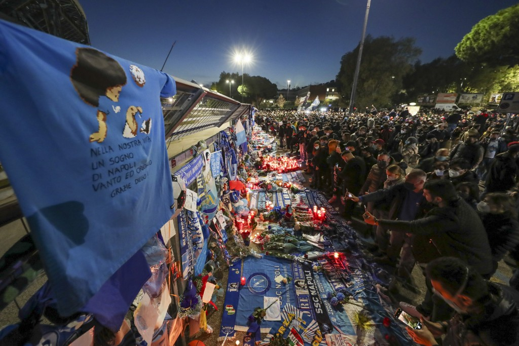 People look memorabilia outside the San Paolo stadium commemorating soccer legend Diego Maradona, in Naples, Thursday, Nov. 26, 2020. Maradona died on...