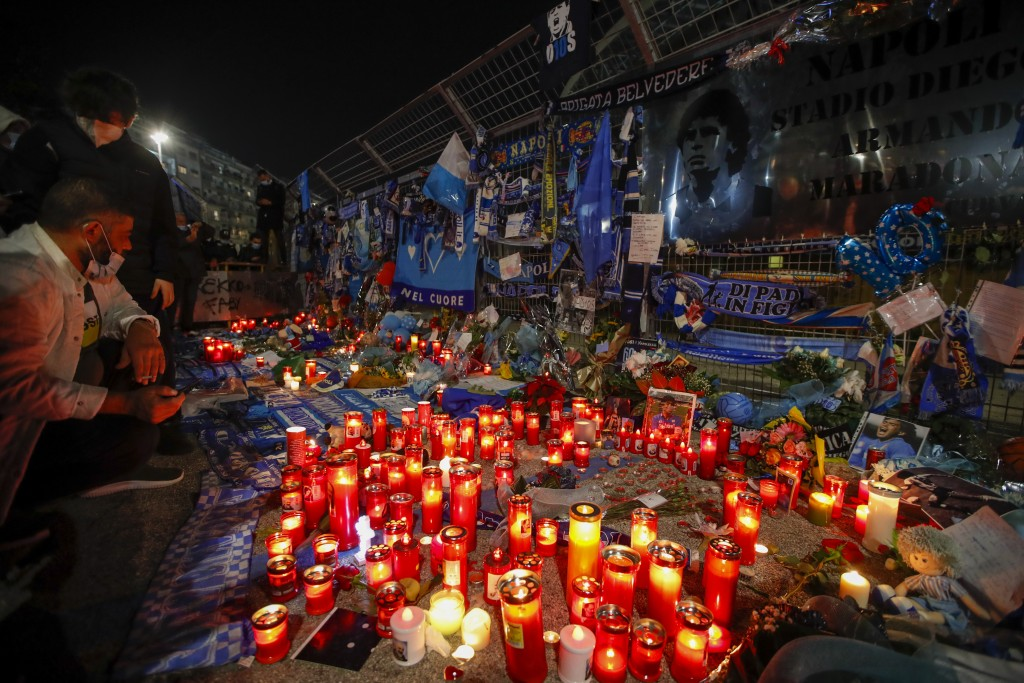 People look at memorabilia outside the San Paolo stadium commemorating soccer legend Diego Maradona, in Naples, Thursday, Nov. 26, 2020. Maradona died...