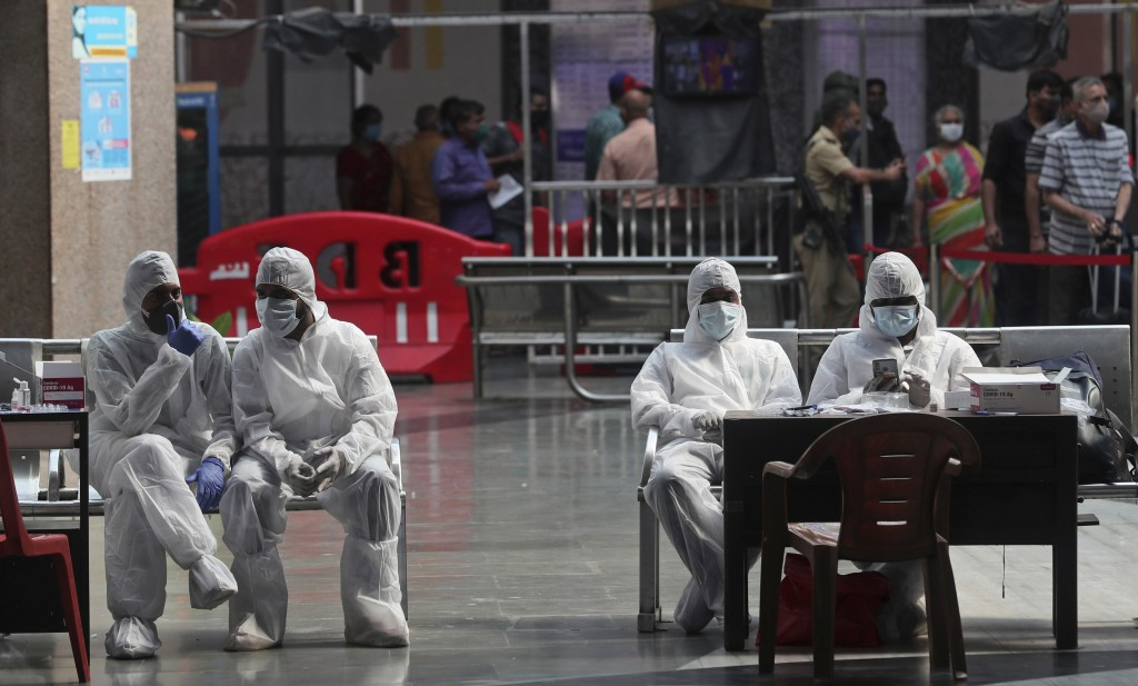 Health workers take a break from taking nasal swab samples from passengers to test for for COVID-19 at a train station in Mumbai, India, Friday, Nov. ...