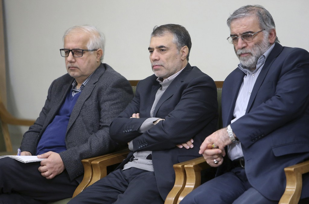 In this picture released by the official website of the office of the Iranian supreme leader, Mohsen Fakhrizadeh, right, sits in a meeting with Suprem...