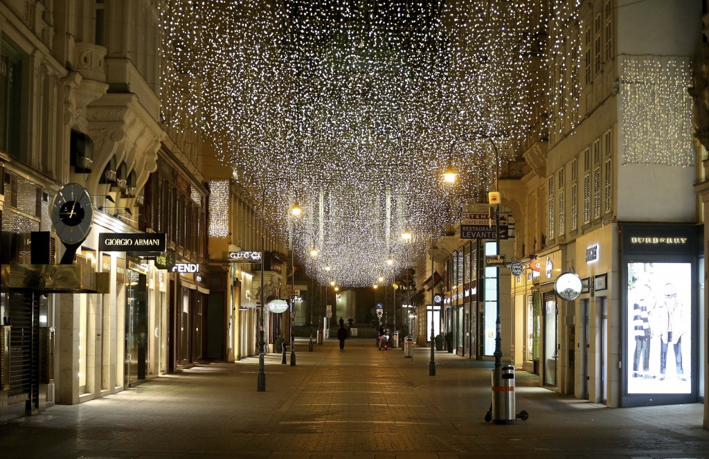FILE - In this Monday, Nov. 23, 2020 file photo, the traditional Christmas lights shine over closed shops in downtown Vienna, Austria. Nations are str...