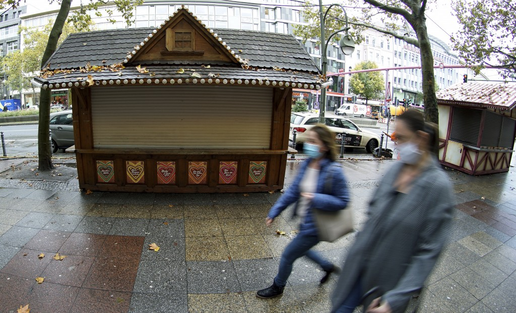 FILE - In this Monday, Nov. 2, 2020 file photo, two woman walk past closed Christmas market booths on a famous shopping road close to the Kaiser Wilhe...