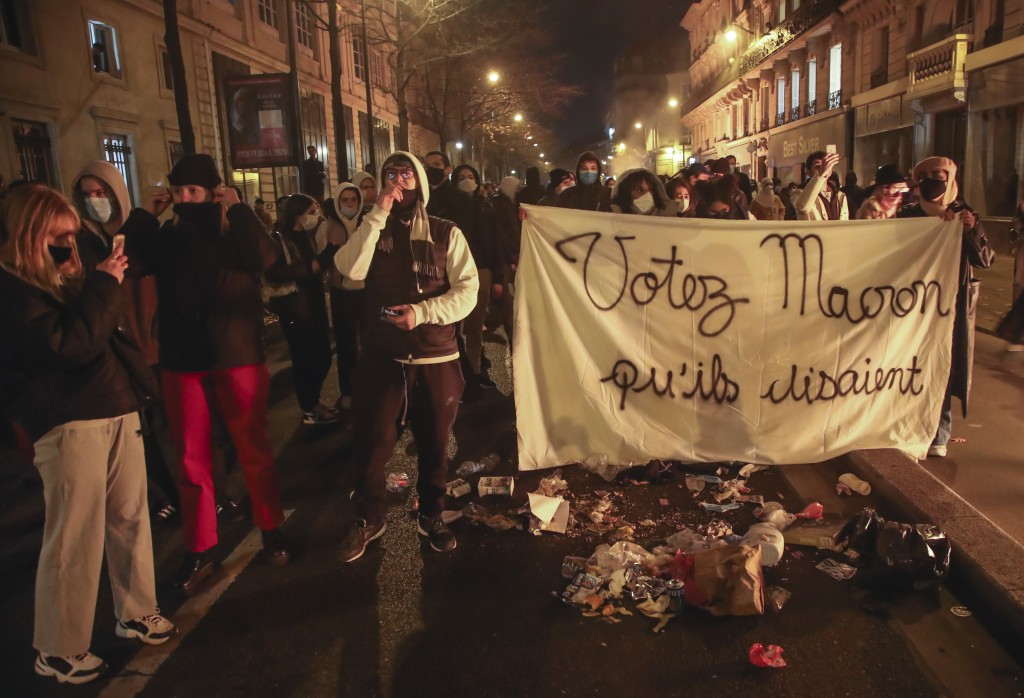 """FILE - In this Tuesday, Nov.24, 2020 file photo, demonstrators march with a banner that reads """"Vote for Macron they said"""", during a rally against poli..."""