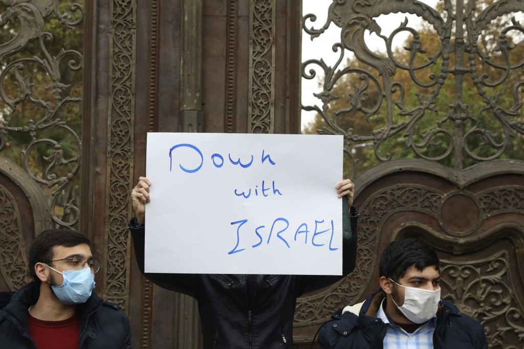 A protester holds an anti-Israeli placard during a gathering in front of Iranian Foreign Ministry on Saturday, Nov. 28, 2020, a day after the killing ...