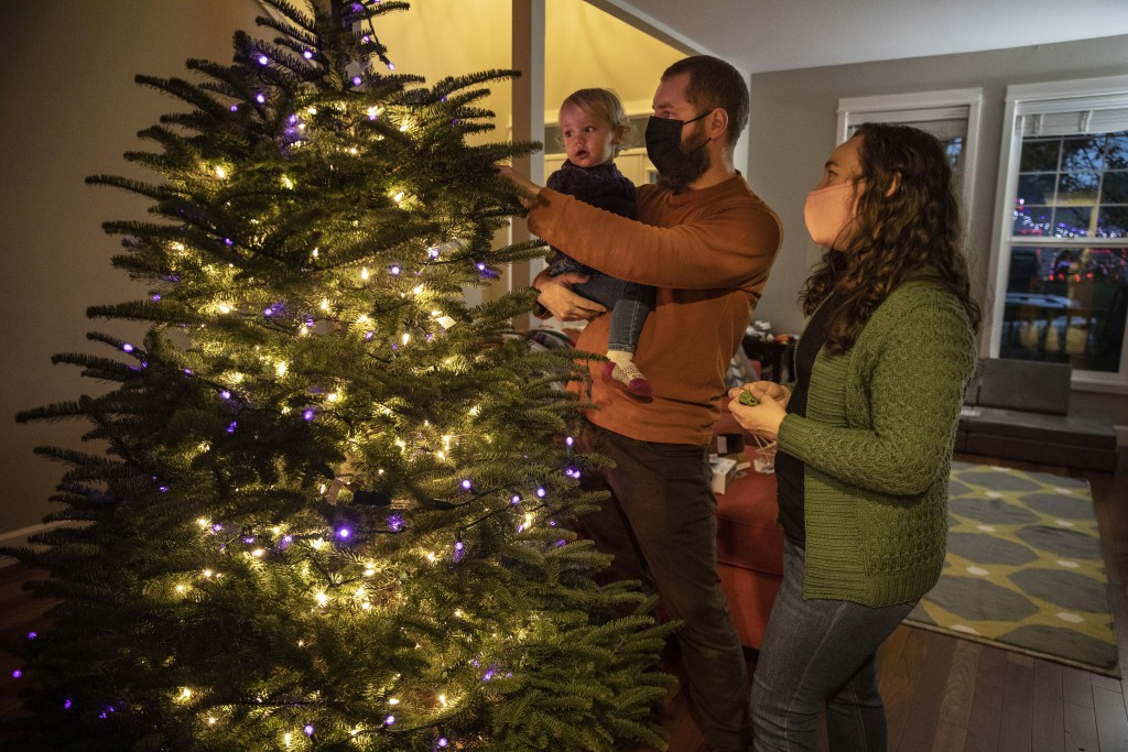 Ani Sirois places lights and decorations on the family's Christmas tree with daughter Ida, 2, and husband, Chadwick, at their home on Tuesday, Nov. 24...