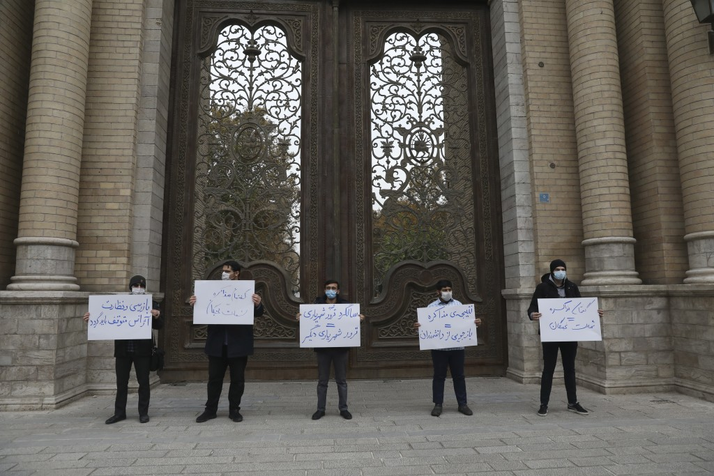 A group of protesters hold placards condemning inspections by the UN nuclear agency (IAEA) on Iran's nuclear activities and the country's nuclear talk...