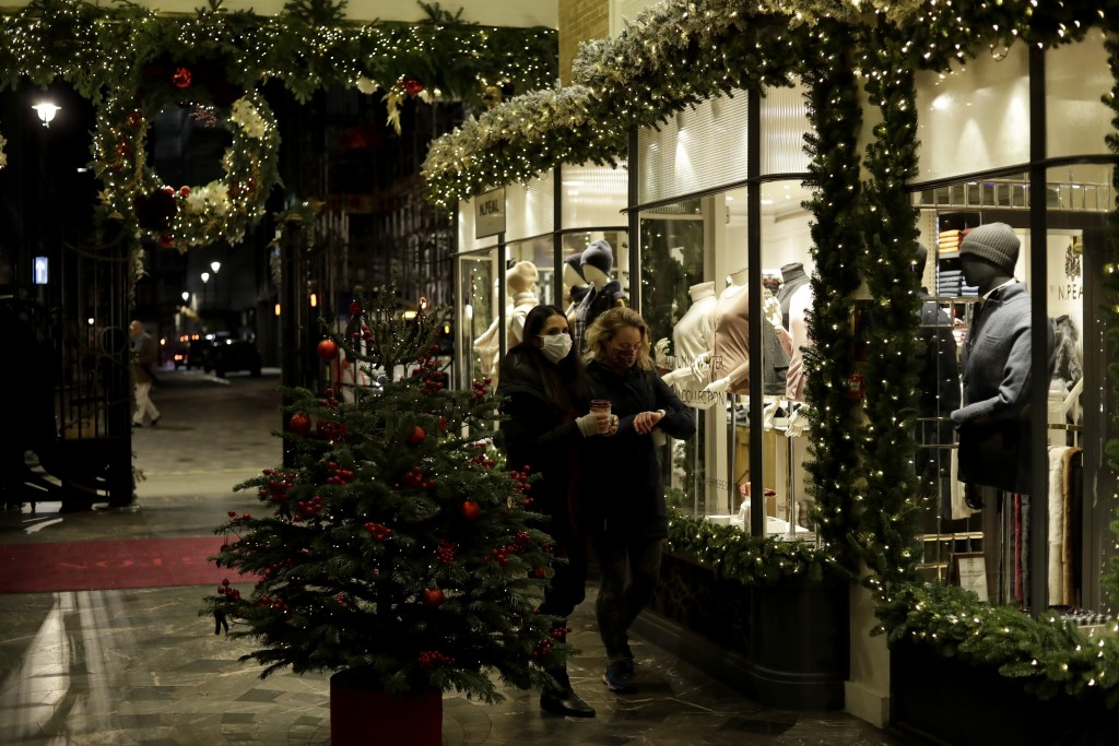 FILE - In this Wednesday, Nov. 25, 2020 file photo, women wearing face masks walk past a Christmas tree and lights in Burlington Arcade, where all non...