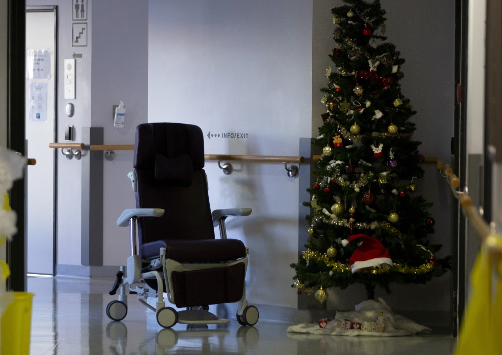 An empty chair is left in a hallway next to a Christmas tree in the COVID-19 ward at the St. Michiel Hospital in Brussels, Tuesday, Nov. 24, 2020. Nat...