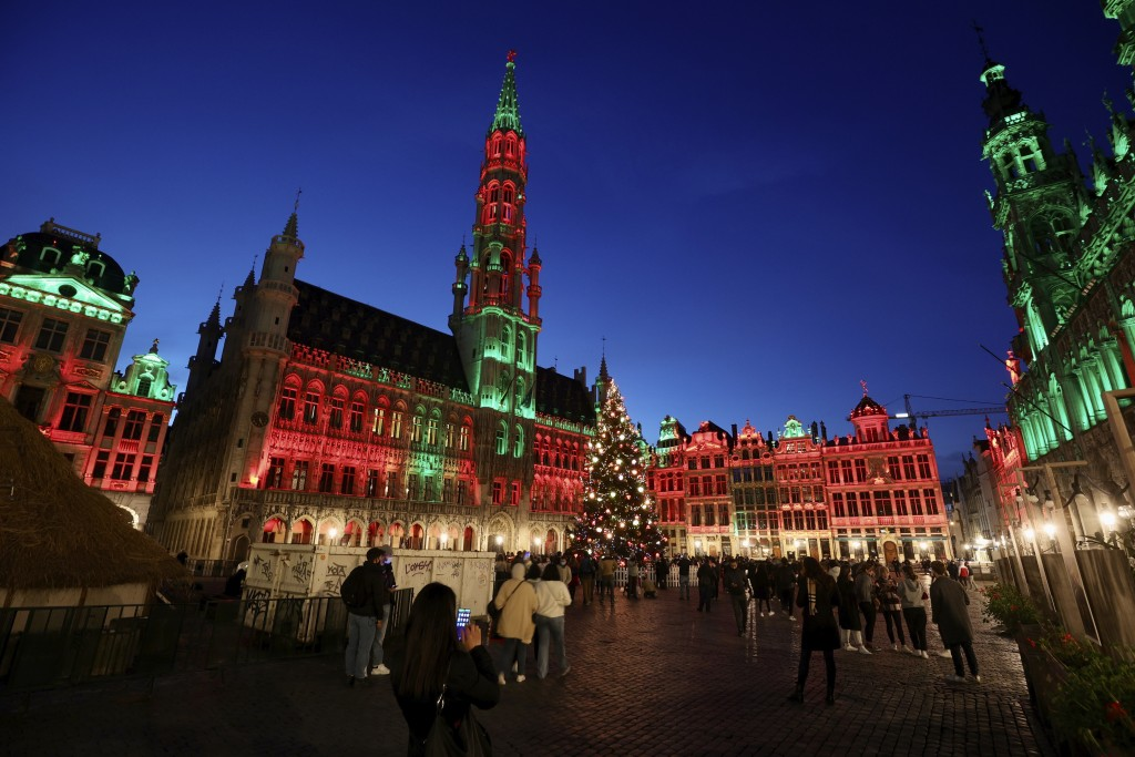 FILE - In this Tuesday, Nov. 24, 2020 file photo, people walk in the historic Grand Place during the official lighting of the Christmas tree in Brusse...