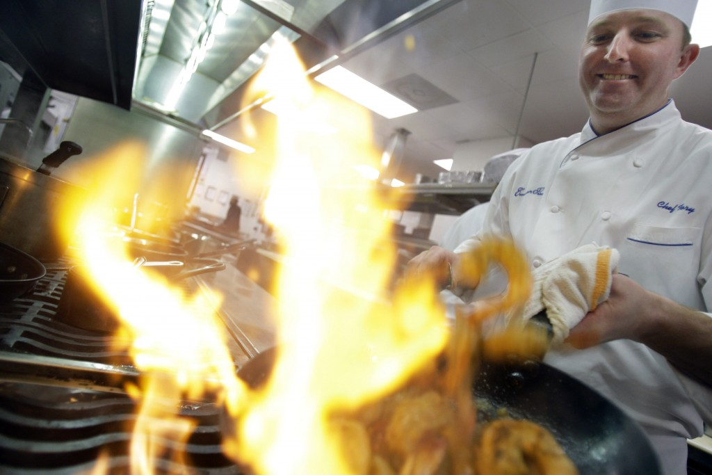 FILE - In this Wednesday, Jan. 7, 2009 file photo, Executive Chef Tory McPhail cooks Lemon and Garlic Crusted Wild Shrimp at Commander's Palace in the...
