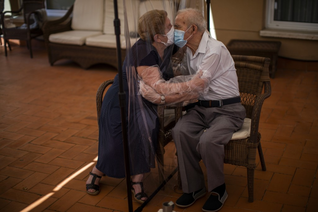 FILE - In this Monday, June 22, 2020 file photo, Agustina Canamero, 81, and Pascual Perez, 84, hug and kiss through a plastic film screen to avoid con...