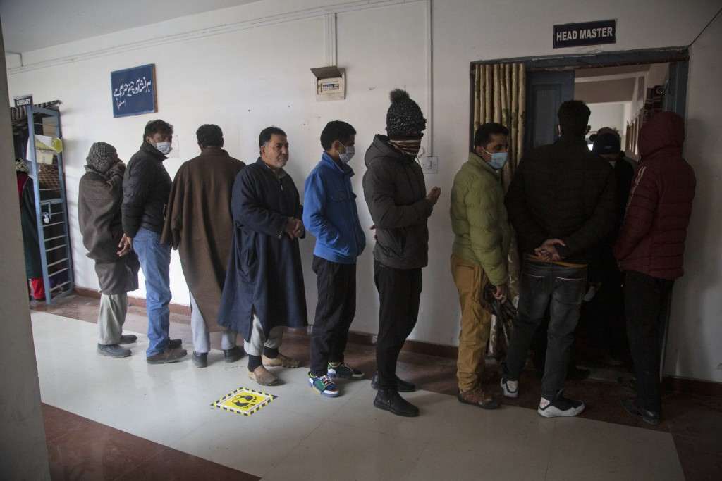 Kashmiris stand in a queue to cast their votes during the first phase of District Development Councils election on the outskirts of Srinagar, Indian c...