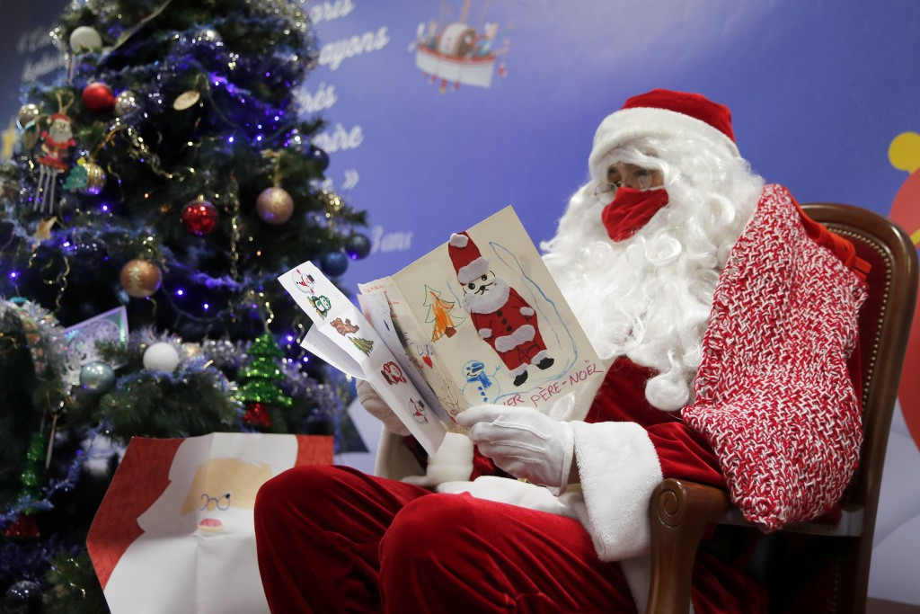 "FILE - In this Monday, Nov. 23, 2020 file photo, a postal worker dressed as Santa, reads letters to addressed to ""Pere Noel"" - Father Christmas in Fre..."