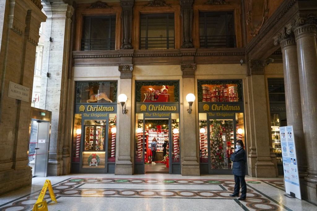 FILE - In this Friday, Nov. 20, 2020 file photo, a security guard stands outside an almost empty Christmas decorations shop, in Rome. Nations are stru...