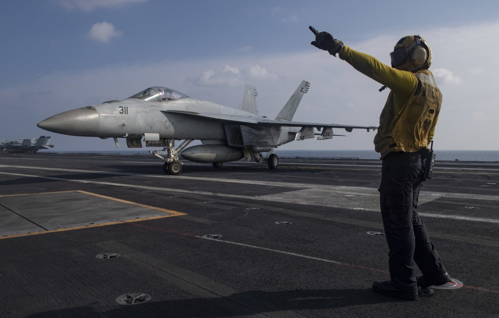 In this photo released by the U.S. Navy, Aviation Boatswain's Mate 3rd Class Marnell Maglasang, from La Puente, Calif., directs an F/A-18E Super Horne...