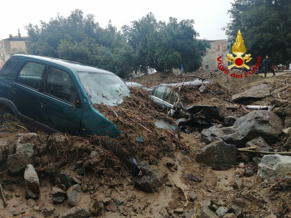 Cars among other debris litter the street in Bitti, Sardinia, Italy, Sunday, Nov. 29, 2020.  The town of Bitti in Sardinia was hit by a storm and floo...