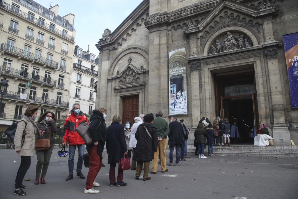 Church-goers wearing face masks as a precaution against the coronavirus lineup outside the Notre-Dame-des-Champs church in Paris, Sunday, Nov. 29, 202...
