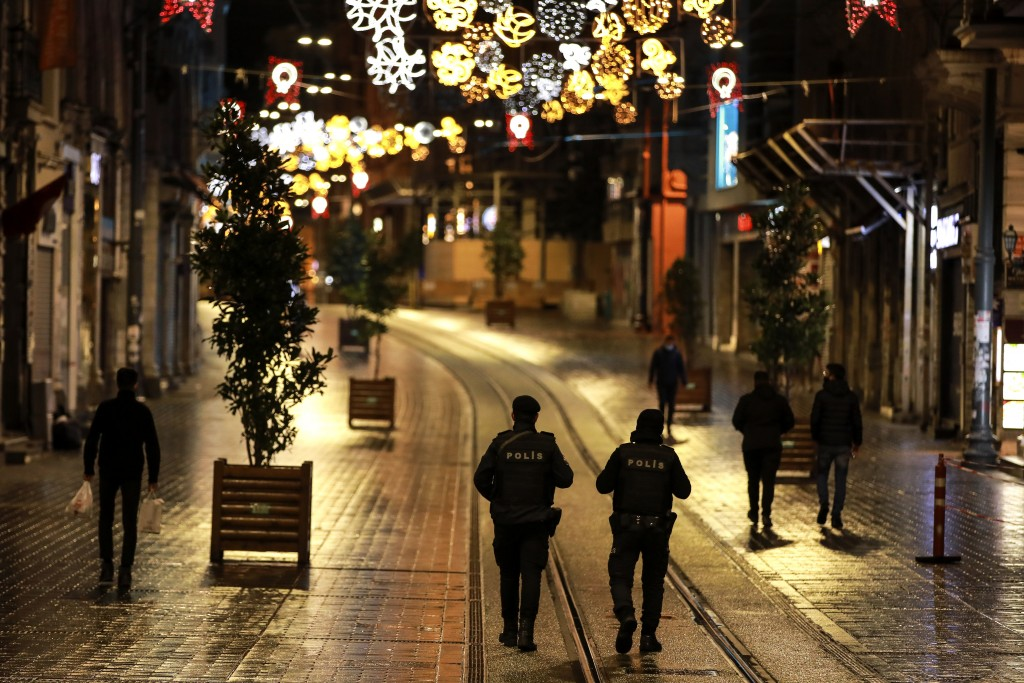 FILE - In this Saturday, Nov. 21, 2020, file photo, police officers patrol Istiklal street, the main shopping street in Istanbul, minutes into the loc...