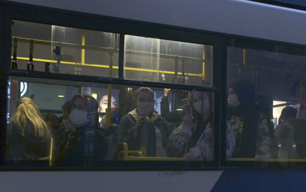 FILE - In this Thursday, Nov. 12, 2020, file photo, commuters wearing masks to help protect against the spread of coronavirus, travel in a bus in Anka...