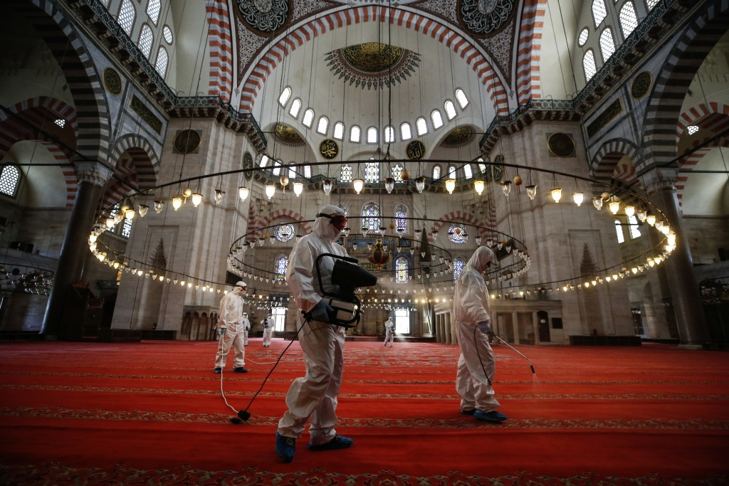 FILE - In this Tuesday, May 26, 2020, file photo, municipality workers disinfect the grounds of the historical Suleymaniye Mosque, in Istanbul, during...