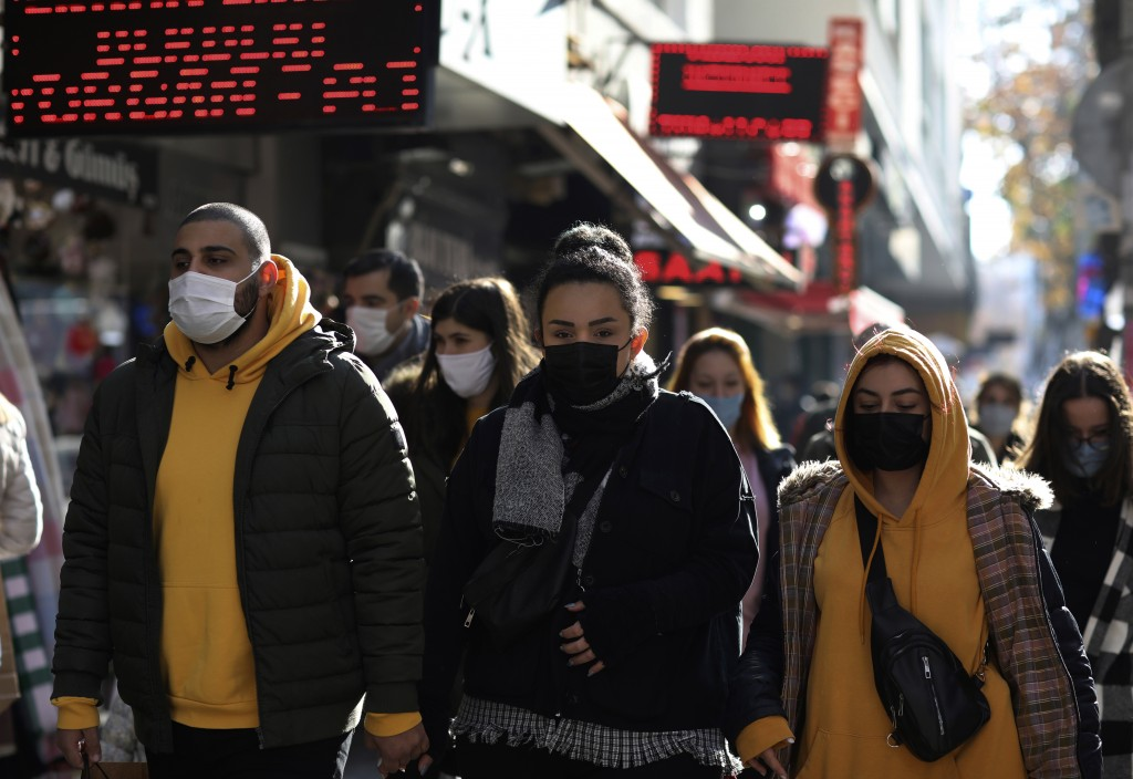People wearing masks to help protect against the spread of coronavirus, walk in Ankara, Turkey, Friday, Nov. 27, 2020. When Turkey changed the way it ...