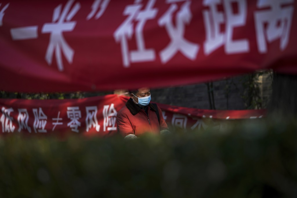 A man wearing a face mask to help curb the spread of the coronavirus walks by propaganda banners displaying coronavirus precaution messages along a ne...