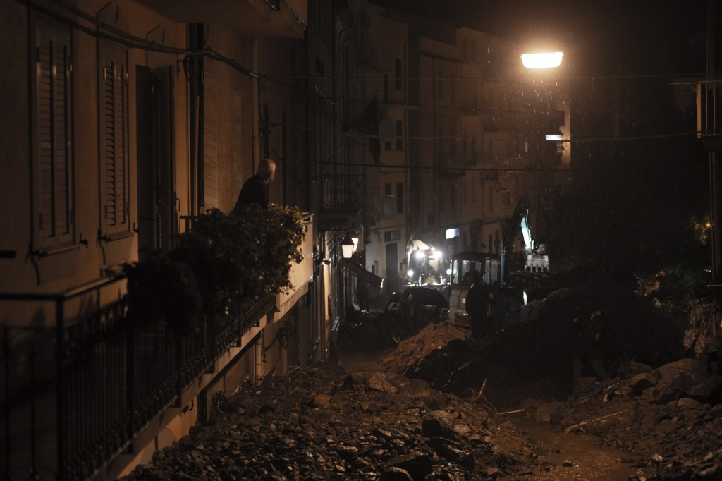 A man looks at the disaster on the street from the balcony of his home in Bitti, Sardinia, Italy, Saturday, Nov. 28, 2020.  The town of Bitti in Sardi...