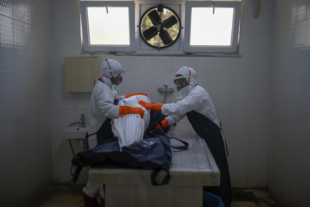 FILE - In this Sunday, May 10, 2020, file photo, female morgue workers, wearing suits, face masks and shield for protection against the coronavirus, p...