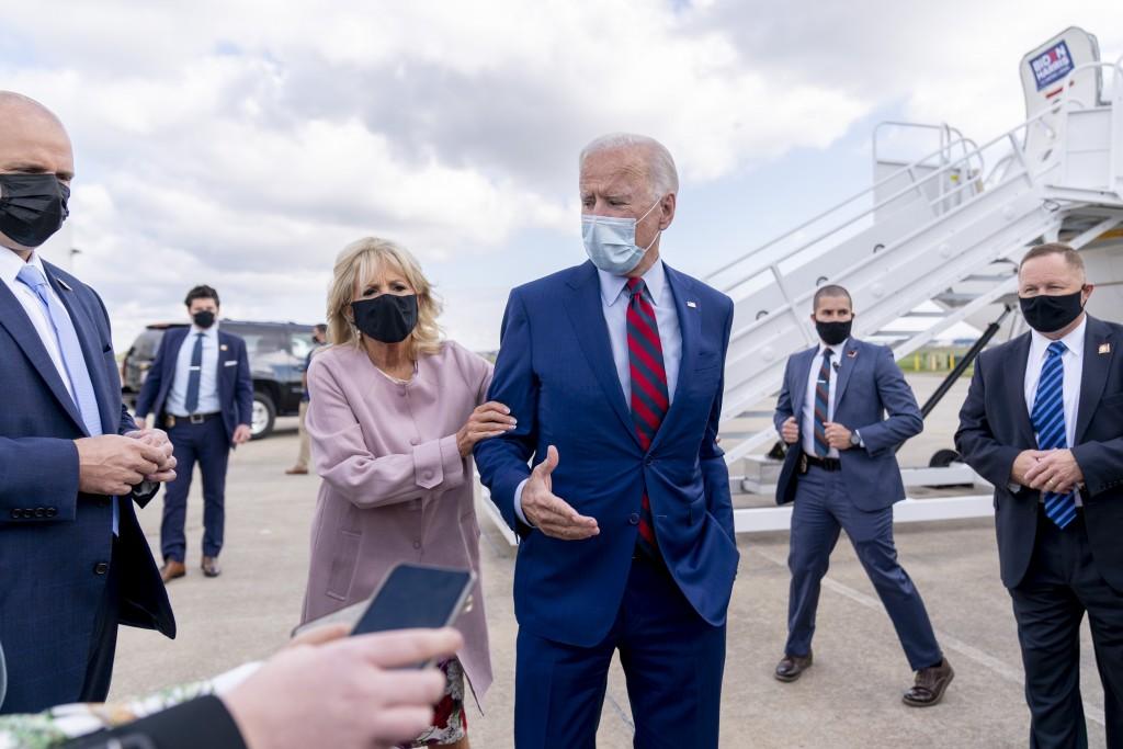 FILE - In this Oct. 5, 2020 file photo, Jill Biden moves her husband, Democratic presidential candidate former Vice President Joe Biden, back from mem...