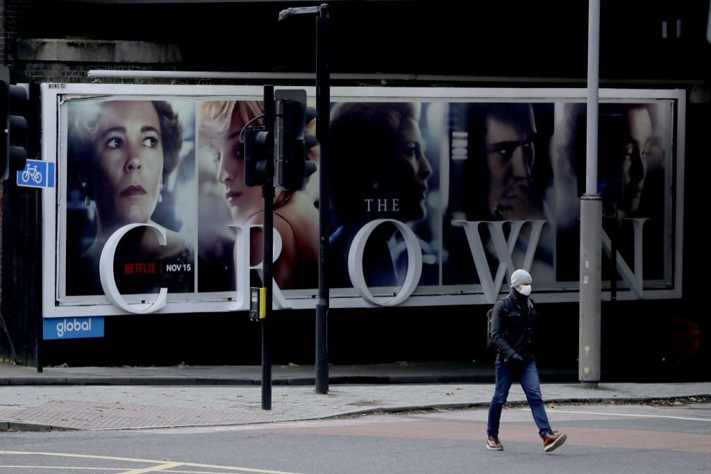 FILE - In this file photo dated Friday, Nov. 20, 2020, a man wearing a face mask walks past a billboard advertising 'The Crown' television series abou...