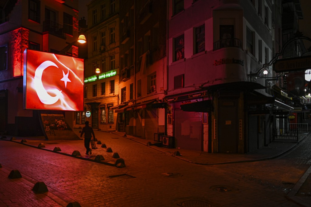 FILE - In this Wednesday, Nov. 25, 2020, file photo, a man walks during a night curfew, due to the virus pandemic, in Istanbul. When Turkey changed th...
