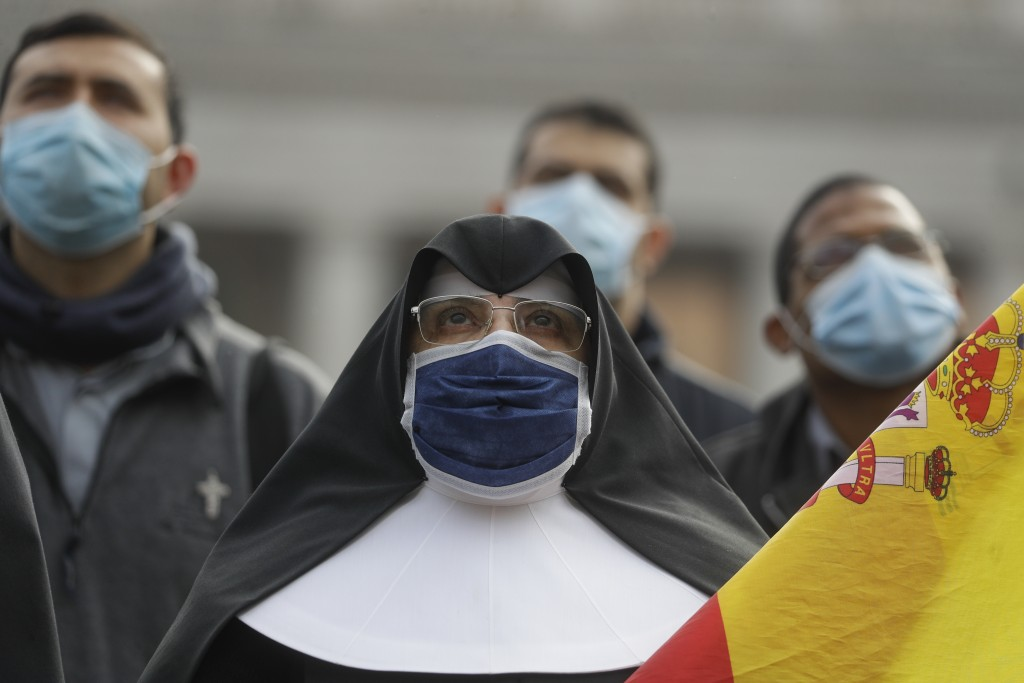 A nun wearing a face mask as she looks up at Pope Francis reciting the Angelus prayer from his studio window overlooking St.Peter's Square at the Vati...