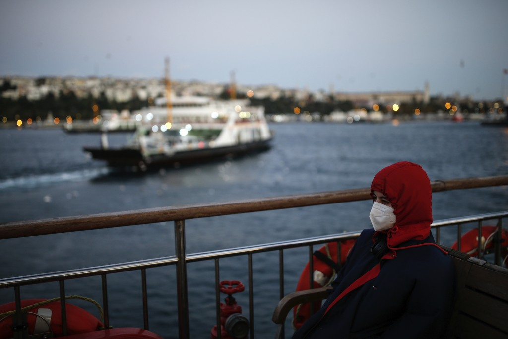FILE - In this Wednesday, Oct. 21, 2020, file photo, a woman, wearing a protective mask to help prevent the spread of the coronavirus, takes a boat tr...