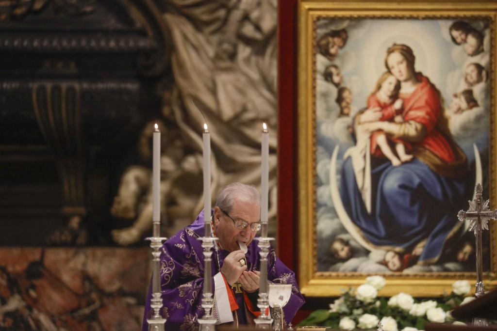 Cardinal Enrico Feroci takes communion as he attends a Mass celebrated by Pope Francis the day after the pontiff raised 13 new cardinals to the highes...