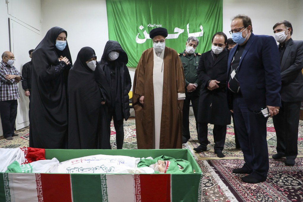 Iran's Judiciary Chief Ayatollah Ebrahim Raisi pays his respect to the body of slain scientist Mohsen Fakhrizadeh among his family, in Tehran, Iran, S...