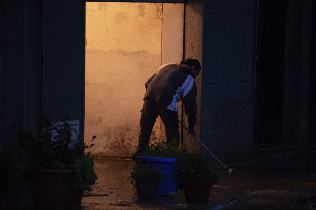 A man man tries to push water and mud out his home in Bitti, Sardinia, Italy, Saturday, Nov. 28, 2020.  The town of Bitti in Sardinia was hit by a sto...