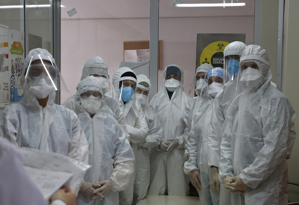 FILE - In this Friday, May 15, 2020, file photo, a team of Turkey's Health Ministry's coronavirus contact tracing team, clad in white protective gear,...