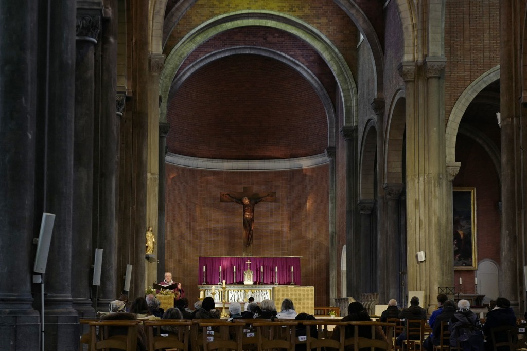 People attend a service in a church, Sunday, Nov. 29, 2020, in Lille, northern France.  People in France are able to go back to their favorite shops a...